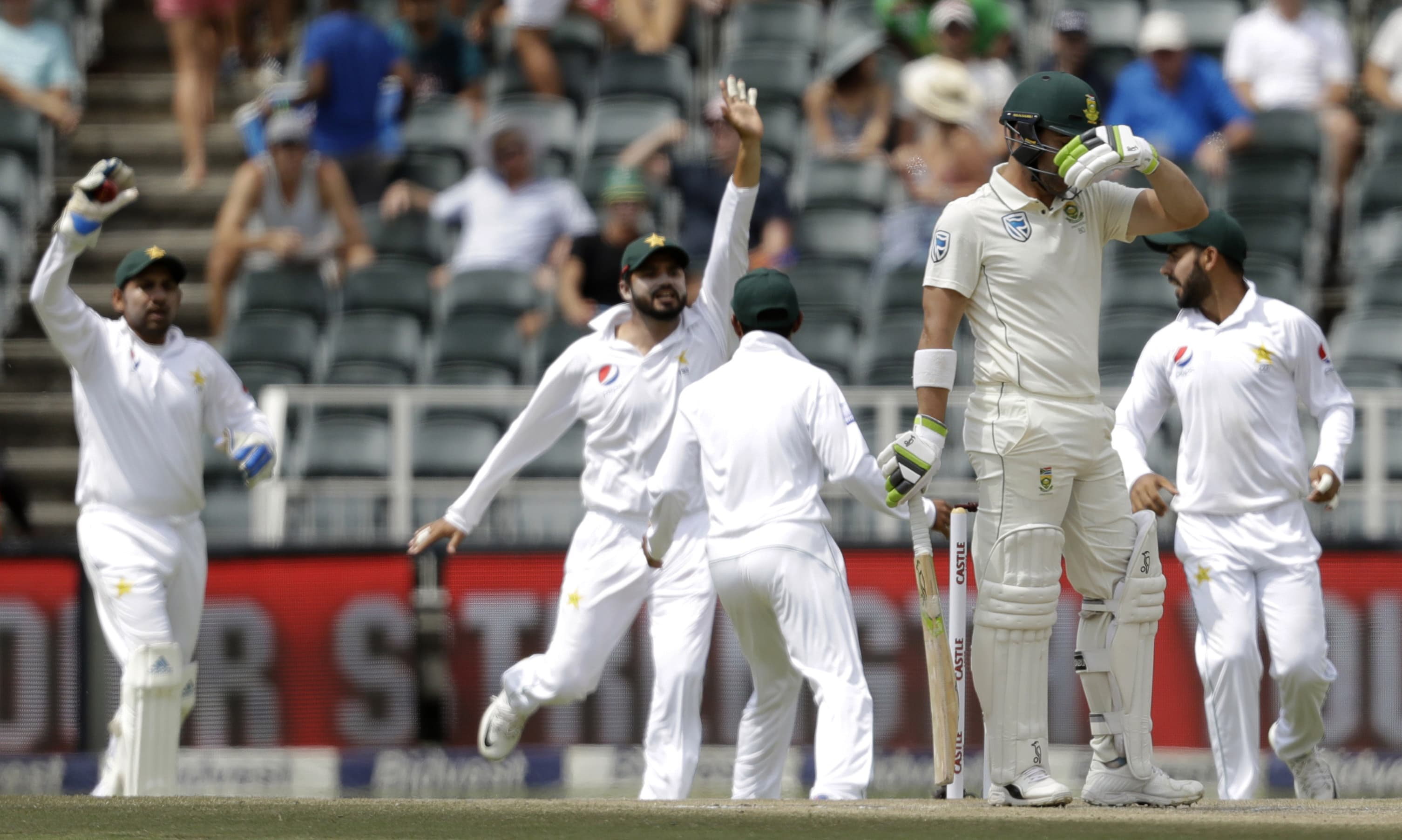 South Africa's batsman Dean Elgar reacts as Pakistan players celebrates his wicket. —AP