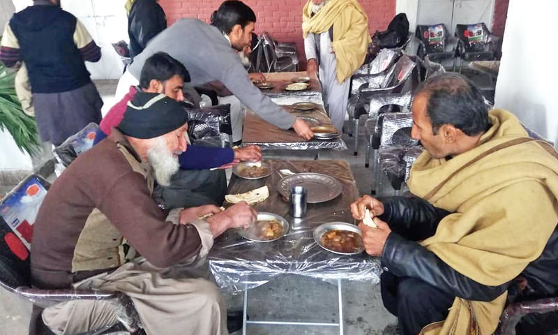 Daily-wage labourers take their meal at the homeless shelter in Tarlai. Islamabad is the only city with fully functional shelters in buildings, with staff deputed there as well. — Photos by the writer
