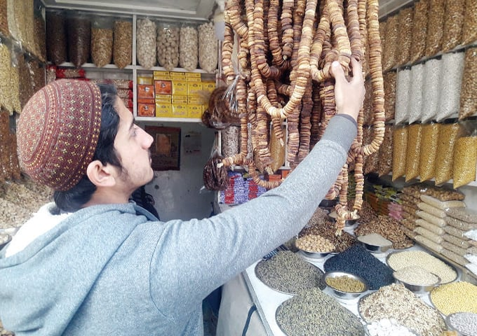 A shopkeeper displays dried figs at his outlet in a Peshawar market. — Dawn