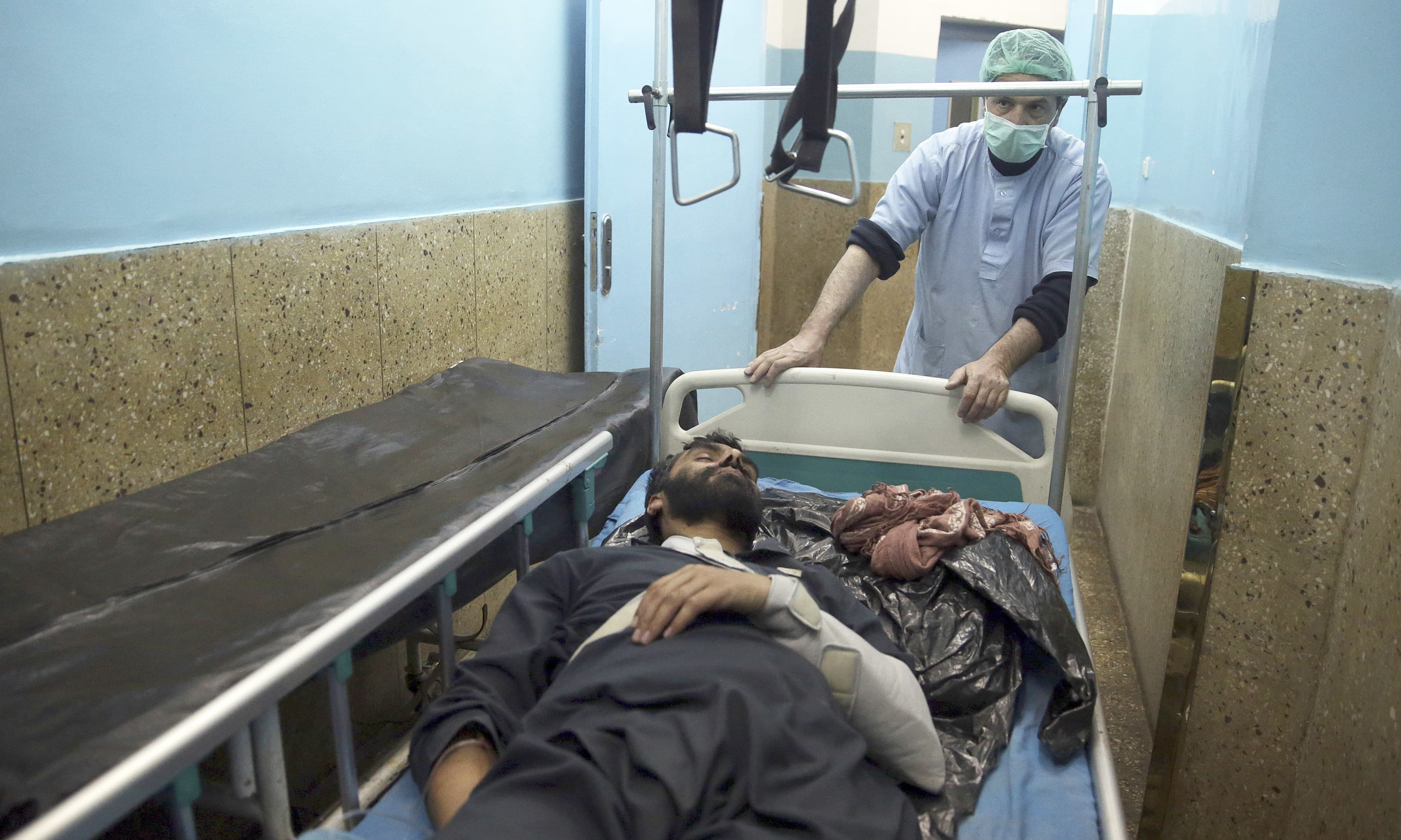 A nurse assists a wounded man in a hospital in Kabul. —AP