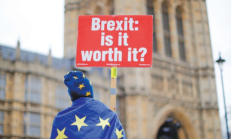 LONDON: An anti-Brexit supporter holds a placard outside the Houses of Parliament on Monday. — AFP