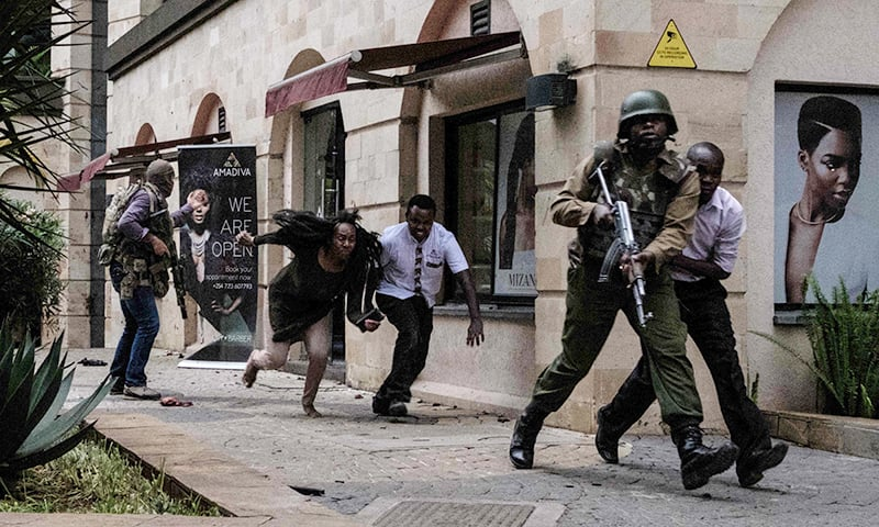 Kenyan personnel help people to escape after a bomb blast at DusitD2 hotel. —AFP
