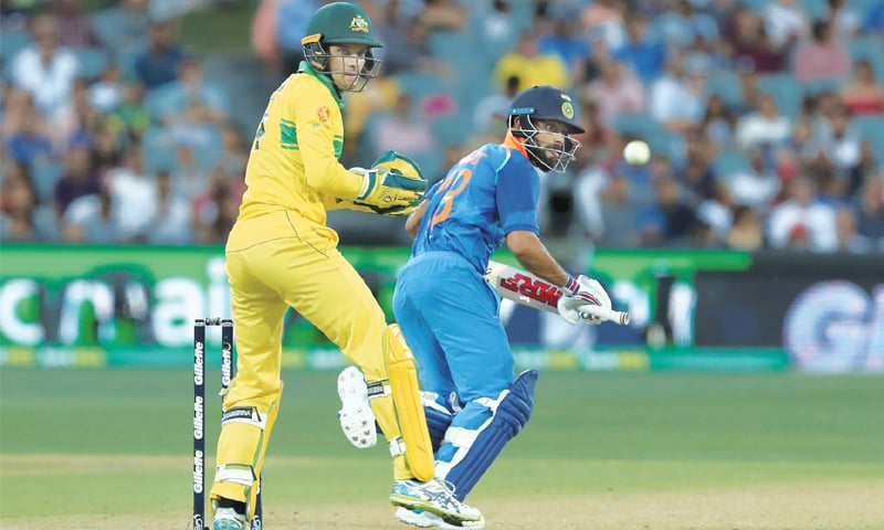 ADELAIDE: Indian skipper Virat Kohli plays a stroke as Australian wicket-keeper Alex Carey looks on during the second One-day International at the Adelaide Oval on Tuesday.—AP