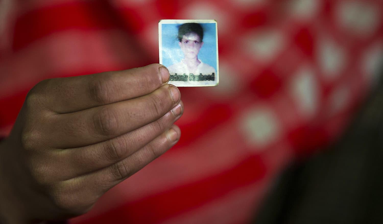 Maimoona Rashid holds the only photograph she has of her brother Mudassir Rashid Parray in Hajin village, north of Srinagar. ─ AP