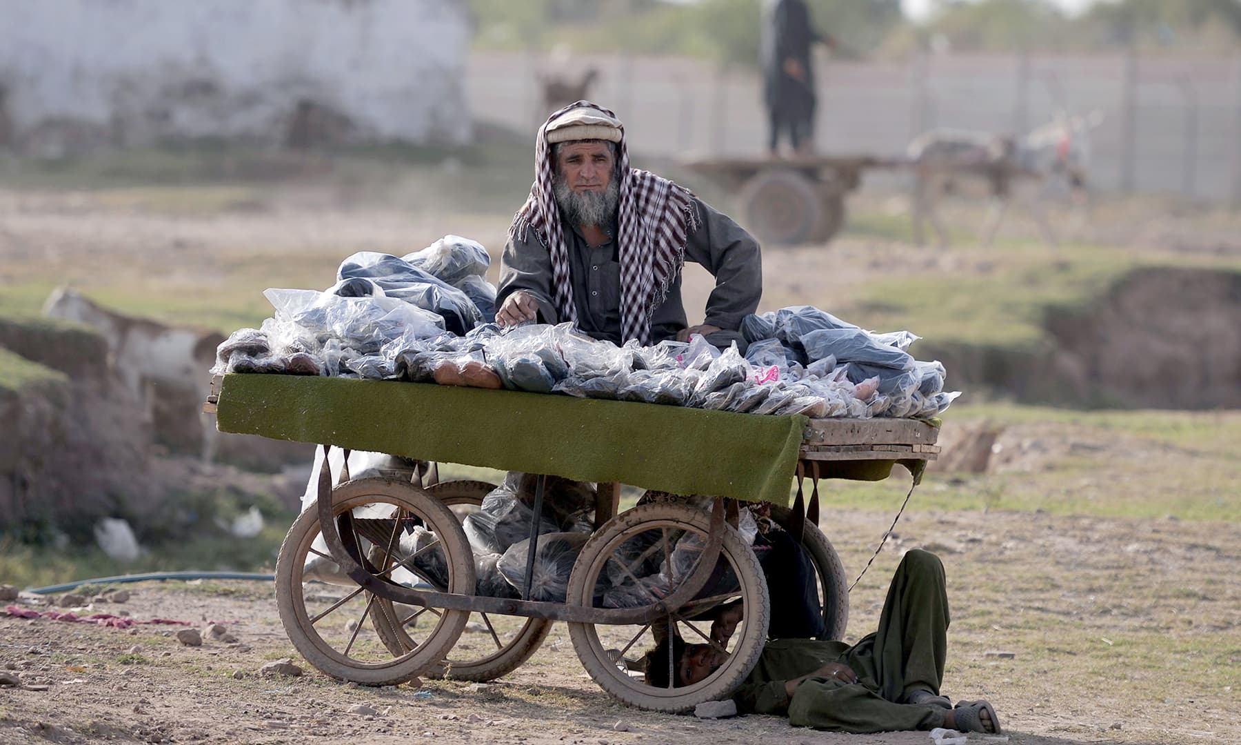An Afghan refugee vendor stands with his cart of products at a refugee camp on the outskirts of Islamabad. — AFP