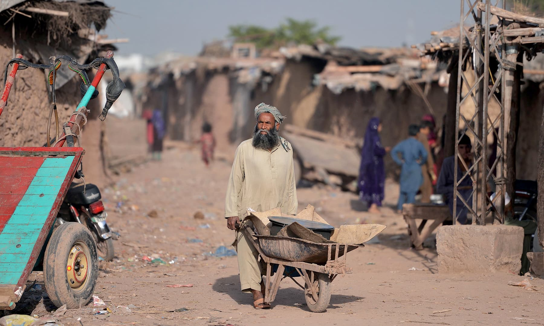 An Afghan refugee vendor pushes a wheelbarrow at a refugee camp on the outskirts of Islamabad. — AFP