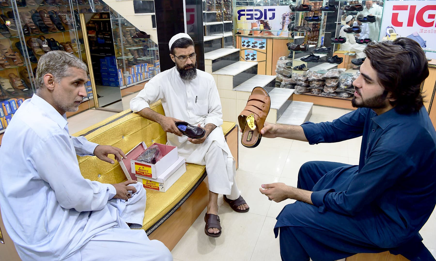 In this picture taken on September 29, 2018 Afghan refugee Shahzad Alam deals with customers at his shoe shop at historic Qissa Khawani bazaar in Peshawar. — AFP