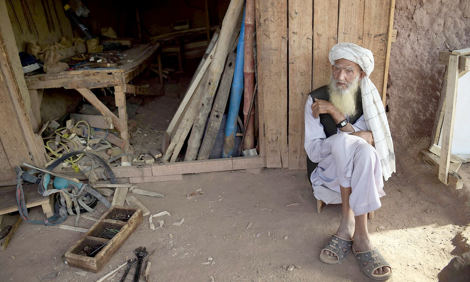 An elder Afghan refugee sit outside a shop at a refugee camp on the outskirts of Islamabad. — AFP