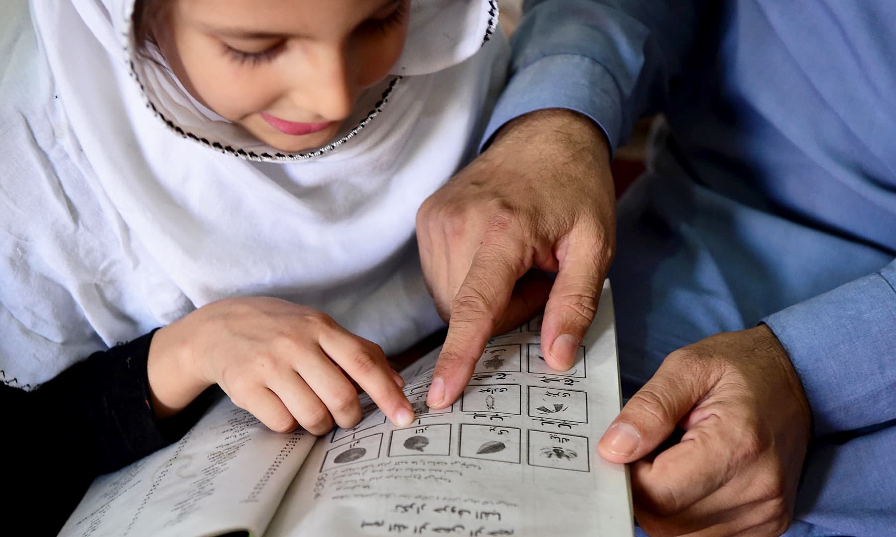Jan's daughter learns to read the Urdu alphabet at her home in Peshawar. — AFP