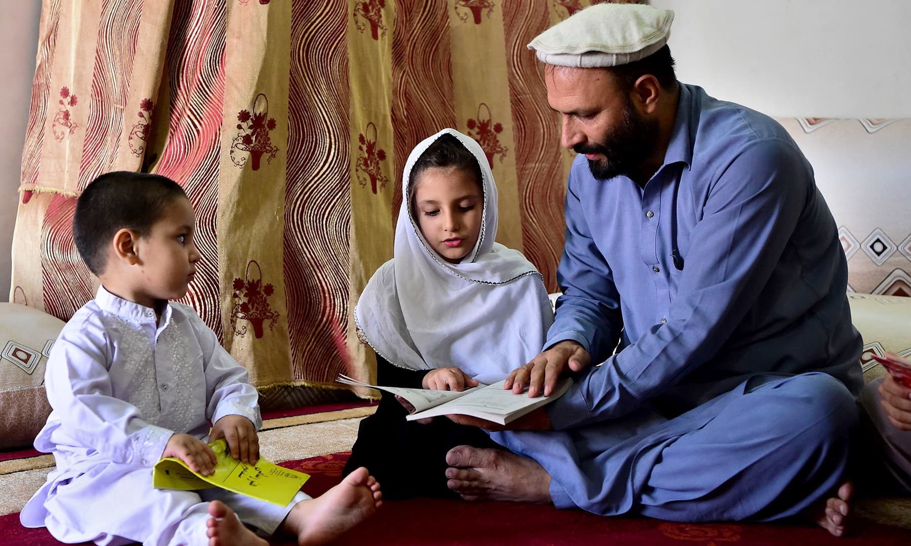 Jan teaches his children at his home in Peshawar. — AFP