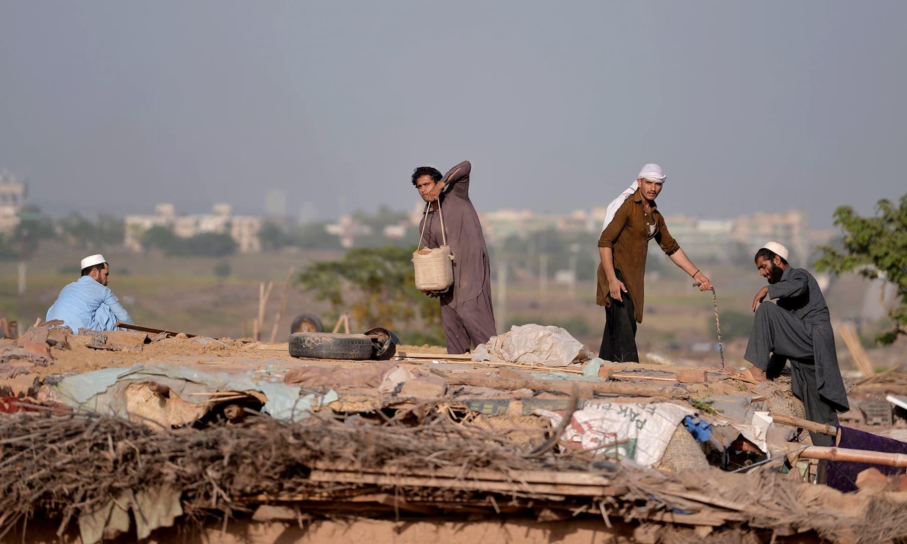 Afghan refugees make a roof for a mud house at a refugee camp. — AFP