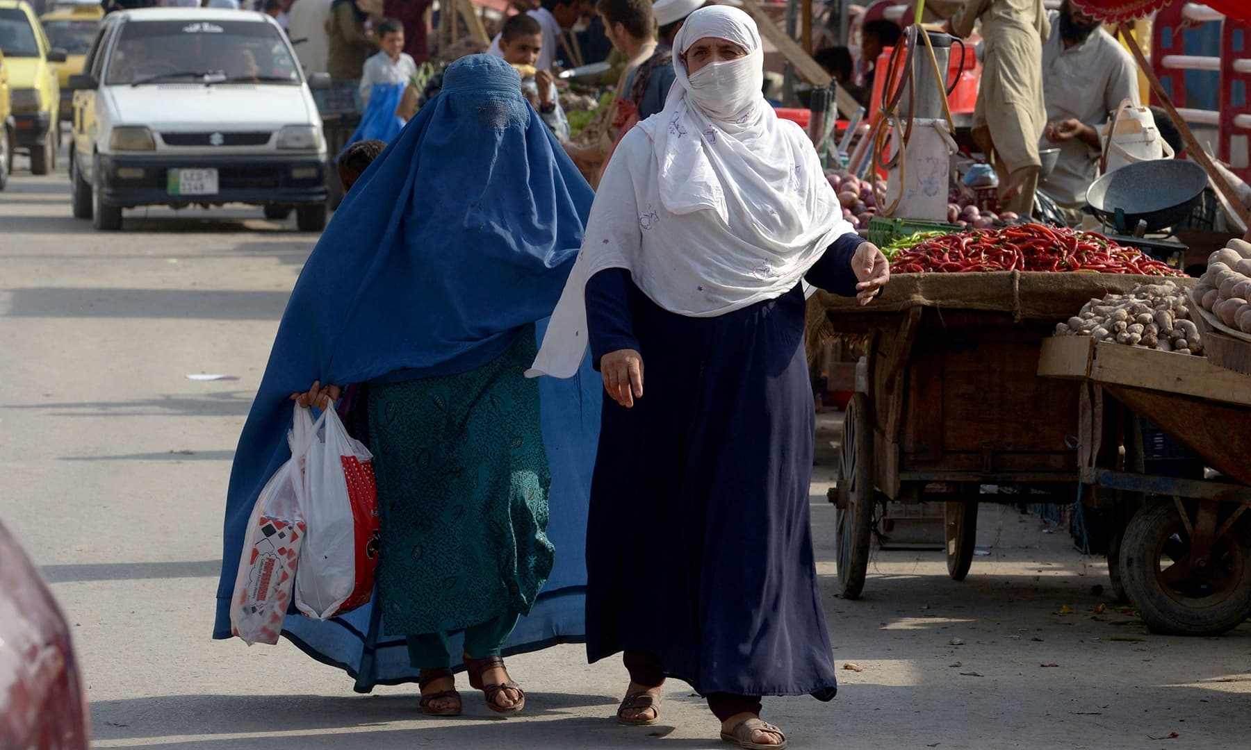 Afghan refugee women walk at a market in Peshawar. — AFP