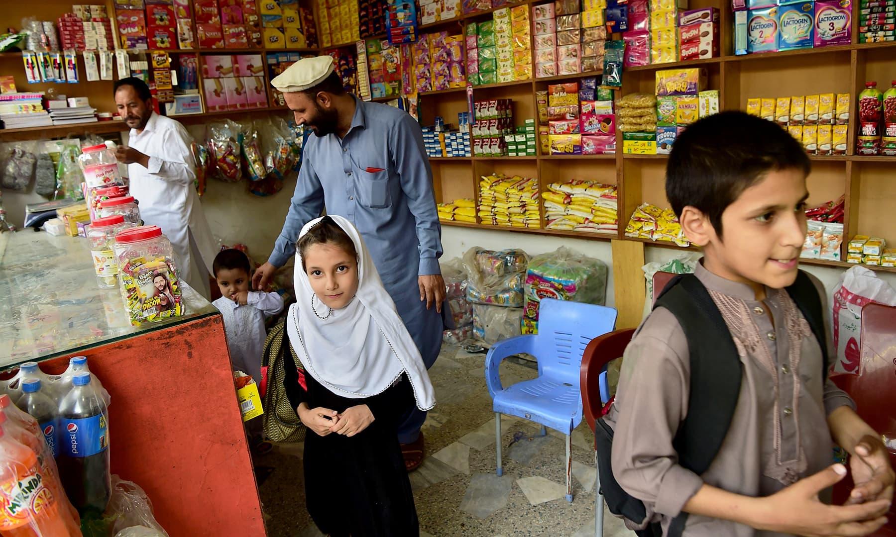 Afghan refugee Ashiqullah Jan visits a shop with his children in Peshawar. — AFP