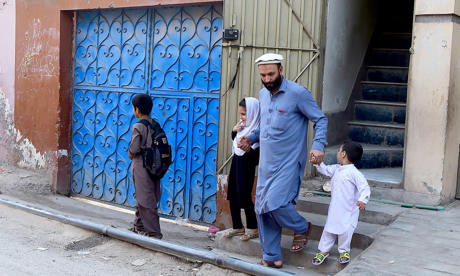 Jan leaves home with his children in Peshawar. — AFP