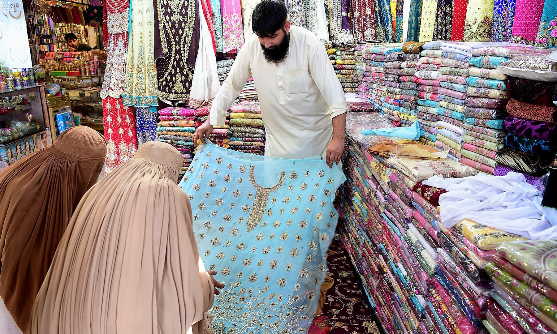 Afghan refugee women check cloth at a shop in the historic Qissa Khawani bazaar in Peshawar. — AFP