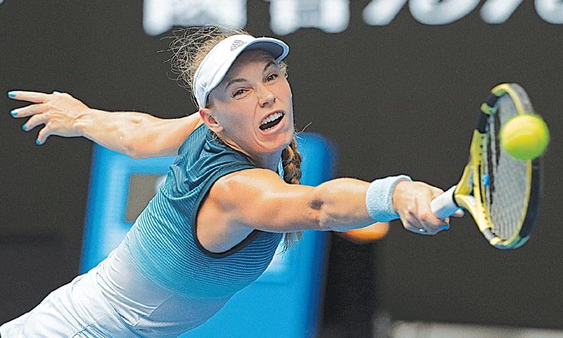 MELBOURNE: Denmark's Caroline Wozniacki hits a backhand return to Maria Sharapova of Russia during their Australian Open third-round match on Friday.—AP