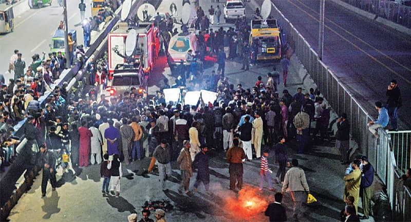 Family members and neighbours of victims who were allegedly killed by the Counter Terrorism Department in Sahiwal block Lahore's Ferozepur Road in protest against the killings.—White Star