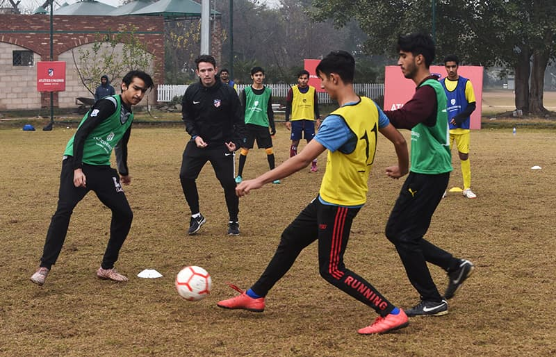 Atletico De Madrid coach Javier Visea (C), 22, trains with Pakistani youths at the club's new facility for developing football in Lahore. ─ AFP