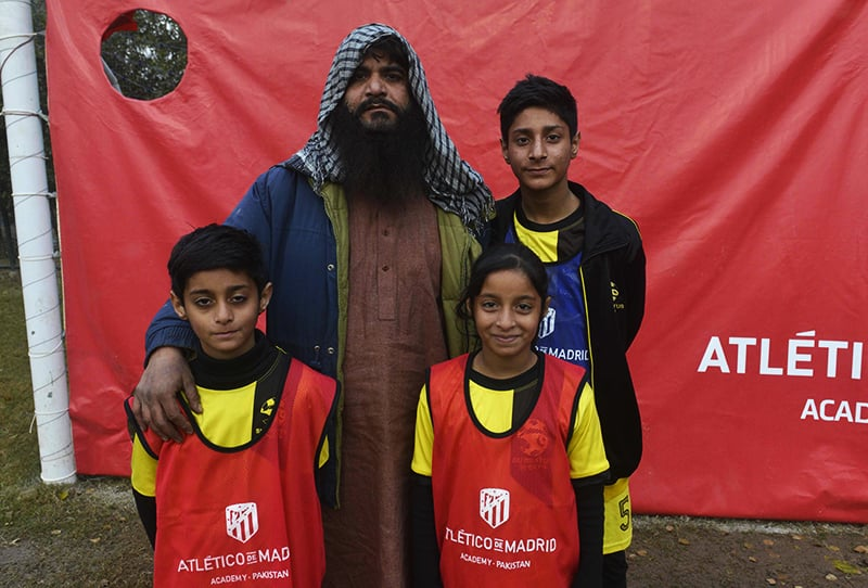 Father Muhammad Shahid (C), poses for a photograph with his daughter Fiza Shahid (front R), 10, and sons Ali Shahid (L), 12 and Warish Shahid (R), 15, at Atletico De Madrid club's new facility for developing football in Lahore. ─ AFP