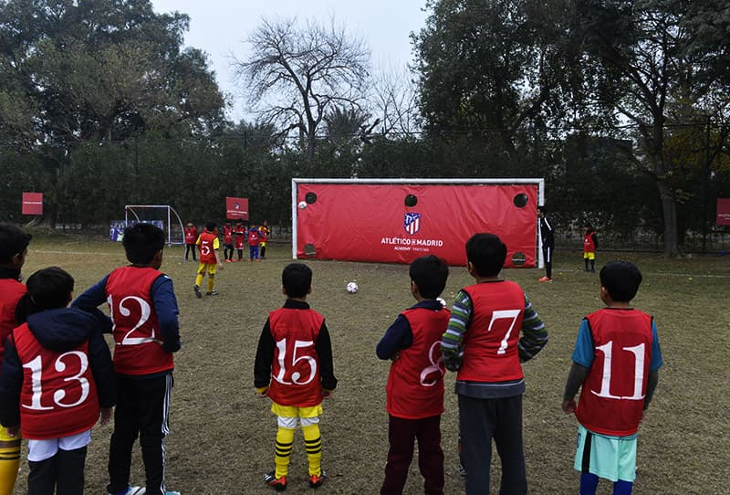 Youths play at Atletico De Madrid club's new facility for developing football in Lahore. ─ AFP