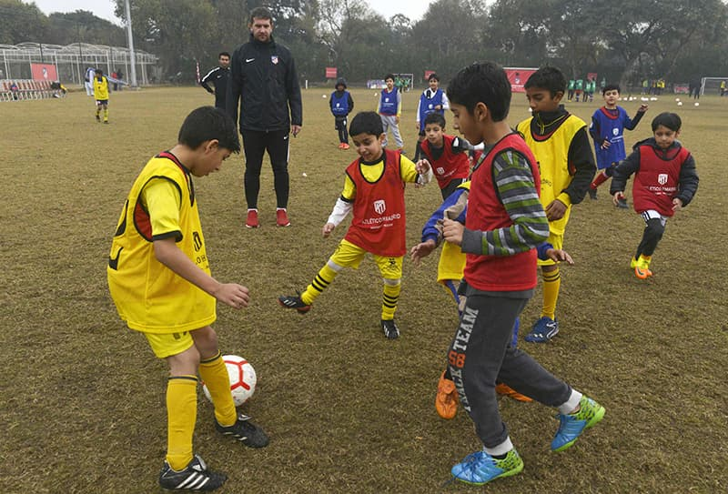 Atletico De Madrid coach Daniel Limones (back L), 32, trains with youths at Atletico De Madrid club's new facility for developing football in Lahore. ─ AFP