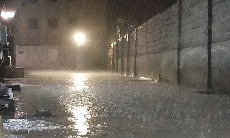 RAINWATER collects in a compound as the city received its  first winter showers on Sunday night. — Photo by Salman Khan