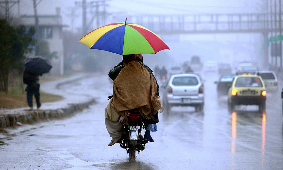 A couple travels on a motorcycle during heavy rain in Rawalpindi. —APP
