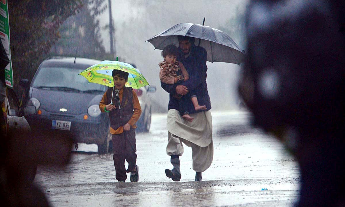 A family walks during heavy rain in Rawalpindi. —APP