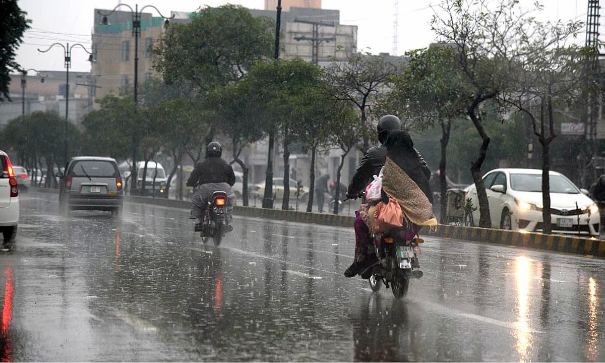 Motorcyclists brave heavy downpour in Lahore. —APP
