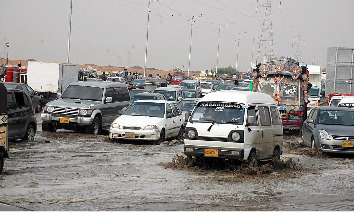 A large number of vehicles passing through rainwater accumulated at Korangi Crossing area of Karachi. —APP