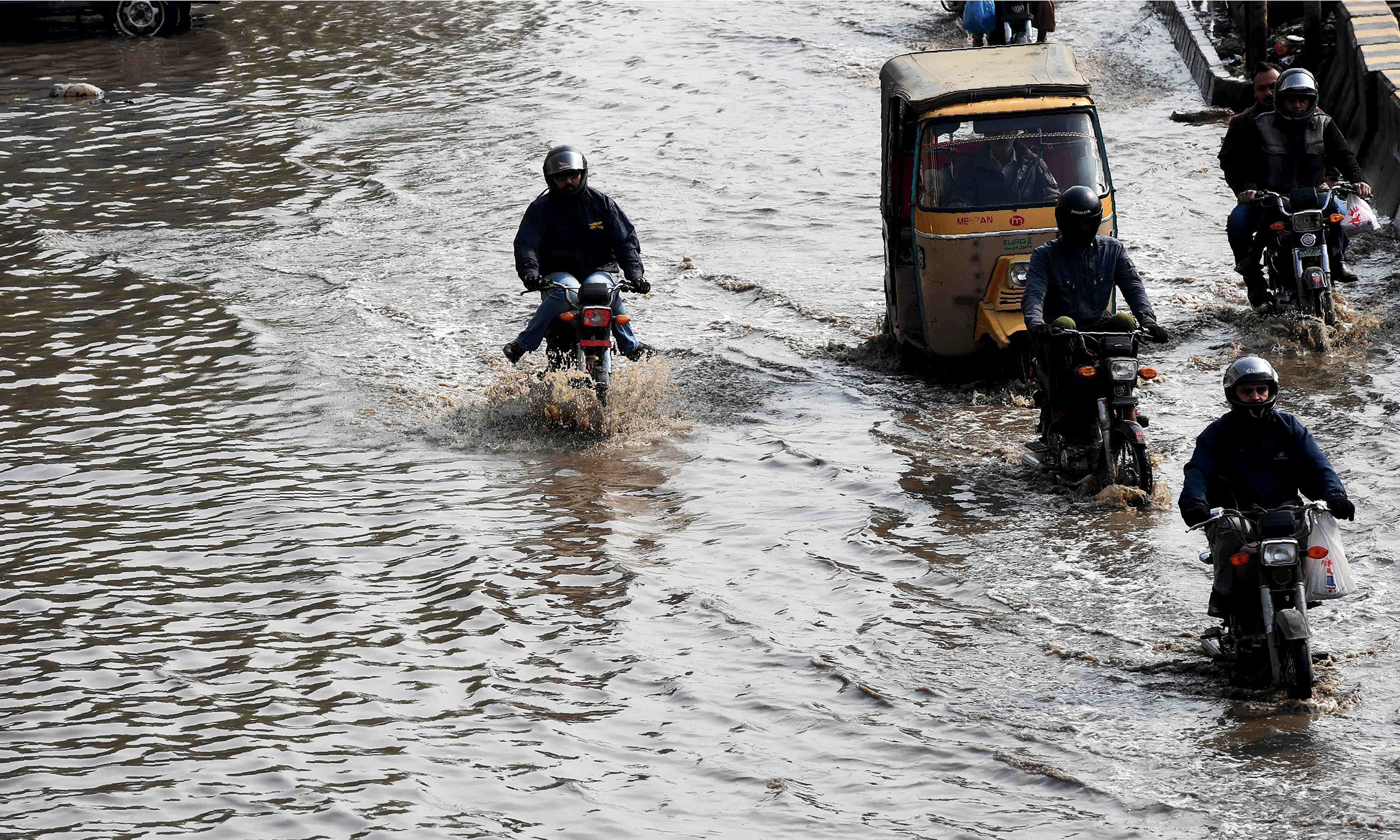 Commuters cross a flooded street after heavy rain in Karachi. —AFP
