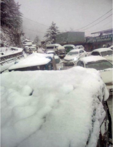 Snow-covered vehcles parked on a road in Murree. — Dawn