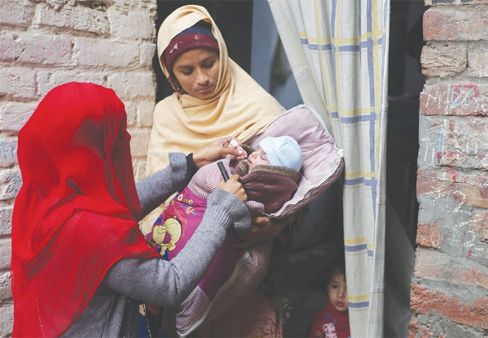 Lahore: A health worker administers polio drops to a child on Monday.—AP