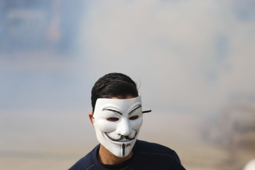 A young man wears a Guy Fawkes mask while facing the forces. Protesters liken themselves with global symbols of protest like this one from the 2005 dystopian political thriller V for Vendetta
