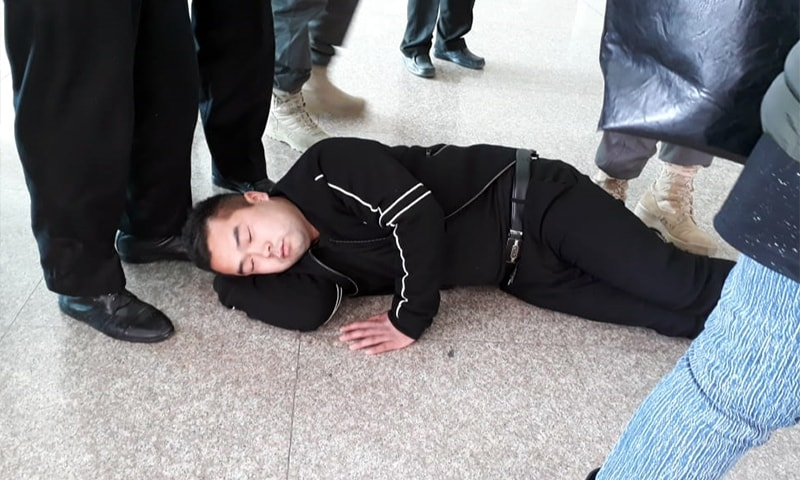 A Chinese passengers lies on the floor in protest against the customs duty at the Islamabad International Airport on Friday. — Photo by author