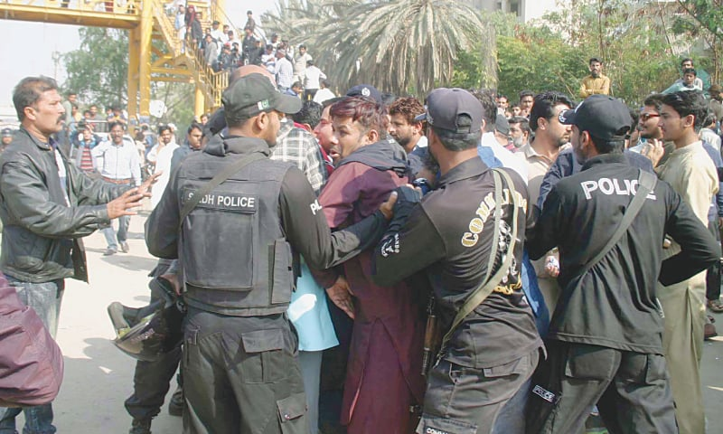 POLICE officers and members of the marriage hall owners' association scuffle near Civic Centre on Saturday.—PPI