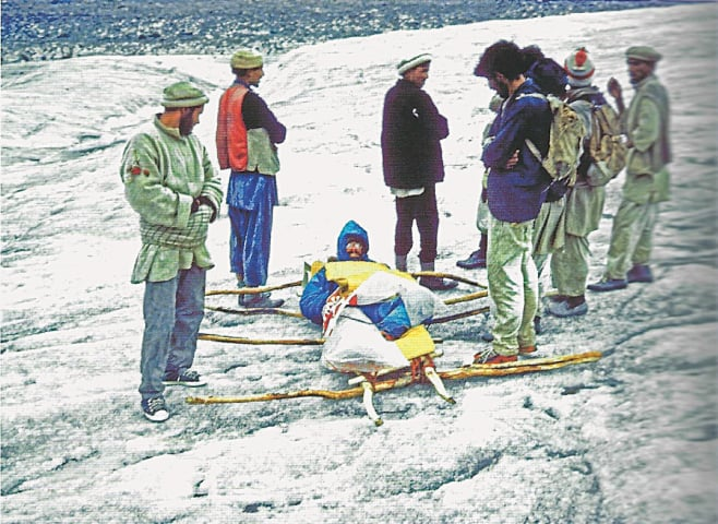 Doug Scott lies on a rudimentary stretcher, surrounded by the Balti porters who carried the injured mountaineer down the Biafo Glacier to within reach of a helicopter. The author broke both legs while abseiling down The Ogre | Photo from the book