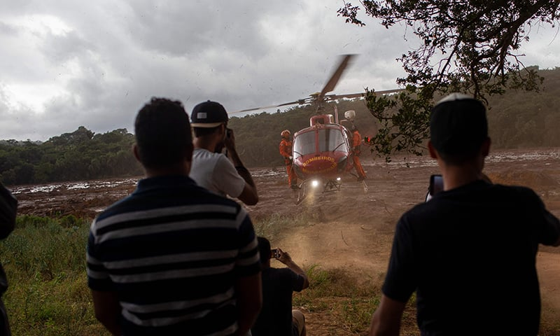 Local residents of the community of Parque das Cachoeiras watch a rescue mission helicopter take off from the mud-covered area a day after the collapse of a dam at an iron-ore mine belonging to Brazil's giant mining company Vale. ─ AFP