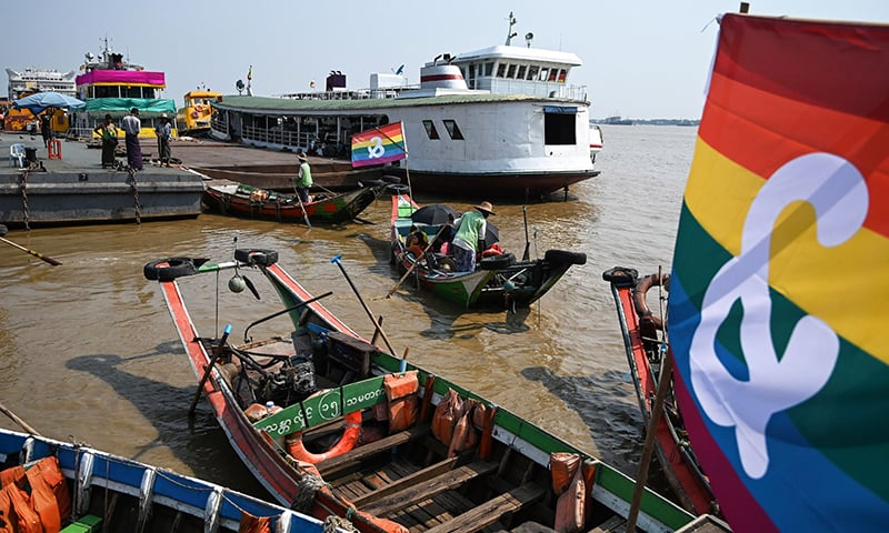 Boatmen prepare wooden boats displaying LBGT community flags near the jetty during the Pride Boat Parade, an event of the Myanmar's Yangon Pride festival in Yangon on January 26. ─ AFP