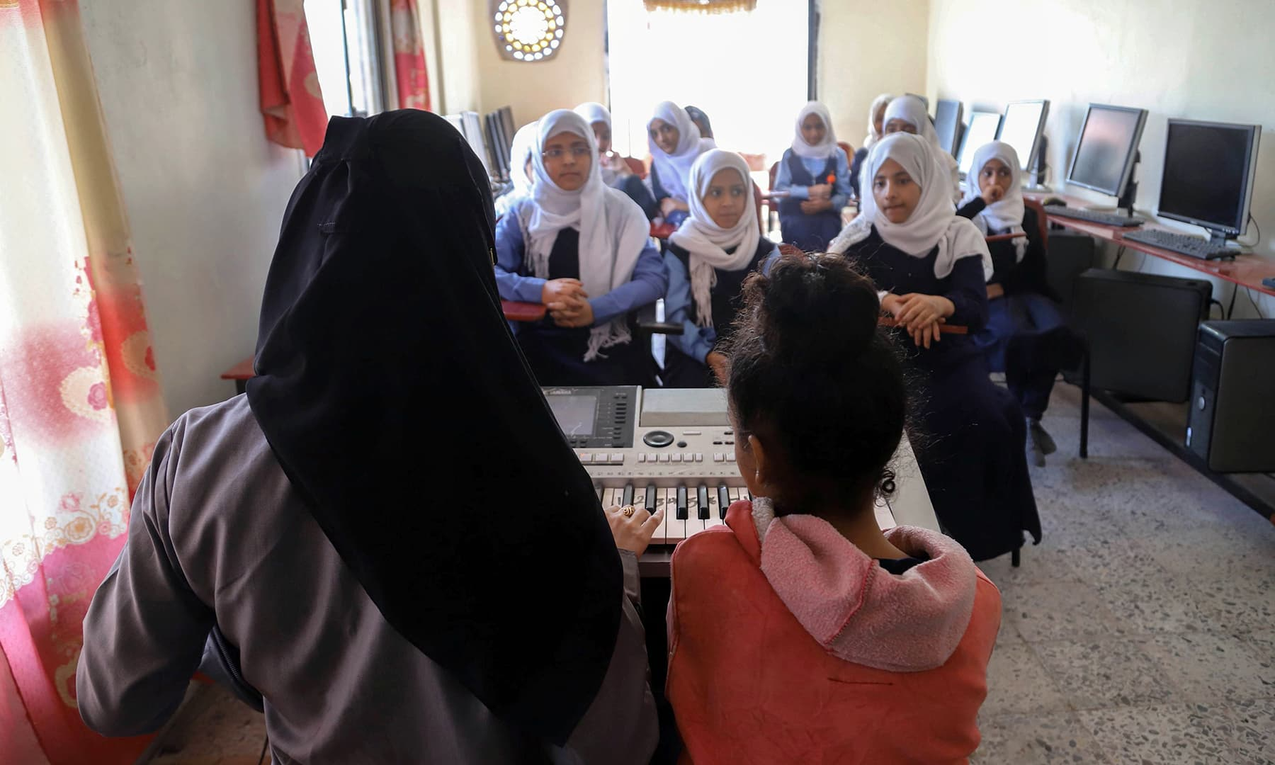 A classroom full of girls eager to put the horrors of war behind them by filling their days with music. — AFP