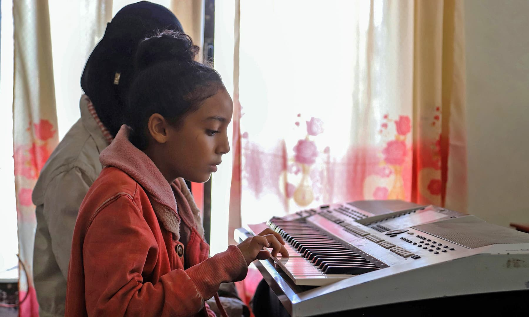 A girl finding reprieve from the ongoing war through piano lessons at Taez city's Al-Nawares school. — AFP