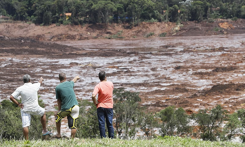 Residents survey an area flooded after a dam that collapsed in Brumadinho, Brazil, Sunday, Jan. 27, 2019. — AP