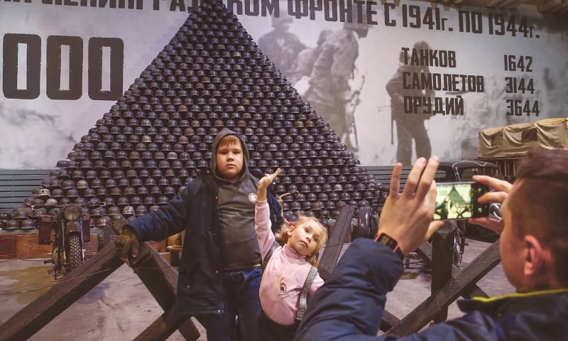 Visitors take pictures in front of a pyramid formed by German soldiers' World War Two helmets at the exhibition dedicated to the 75th anniversary since Leningrad siege was lifted.—Reuters