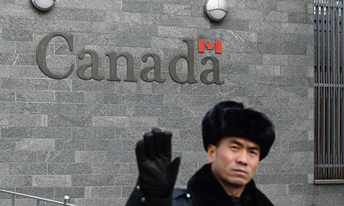 A guard attempts to block photos from being taken outside the Canadian embassy in Beijing on January 27, 2019. — AFP