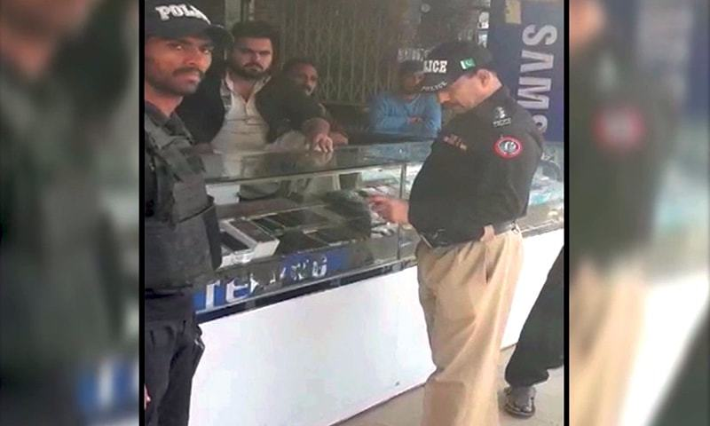 A police official is seen at a mobile phone shop inside the . — DawnNewsTV