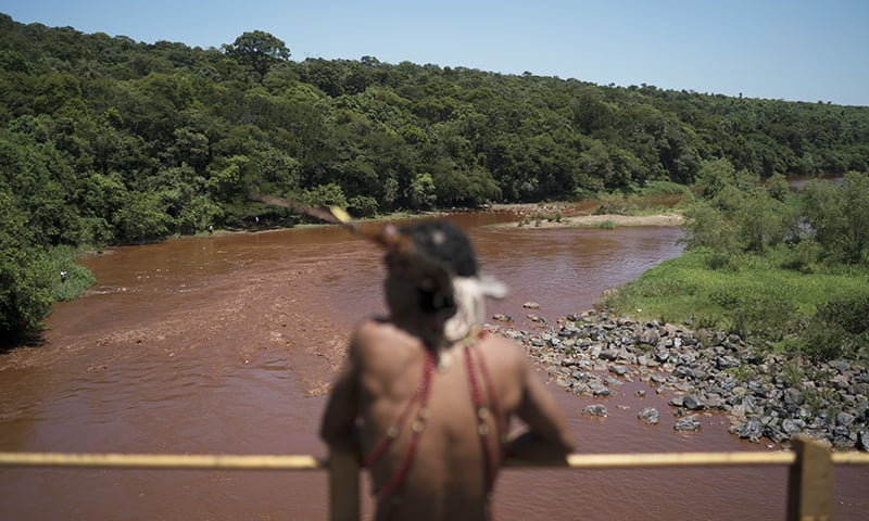Hayo, chief of the Pataxo Ha-ha-hae indigenous community, stands over the Paraopeba River that has turned brown due to contamination from a dam breach. — AP