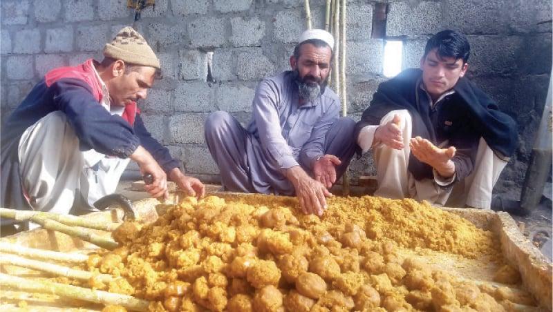 Farmers make gur near their farm in Swabi. — Dawn