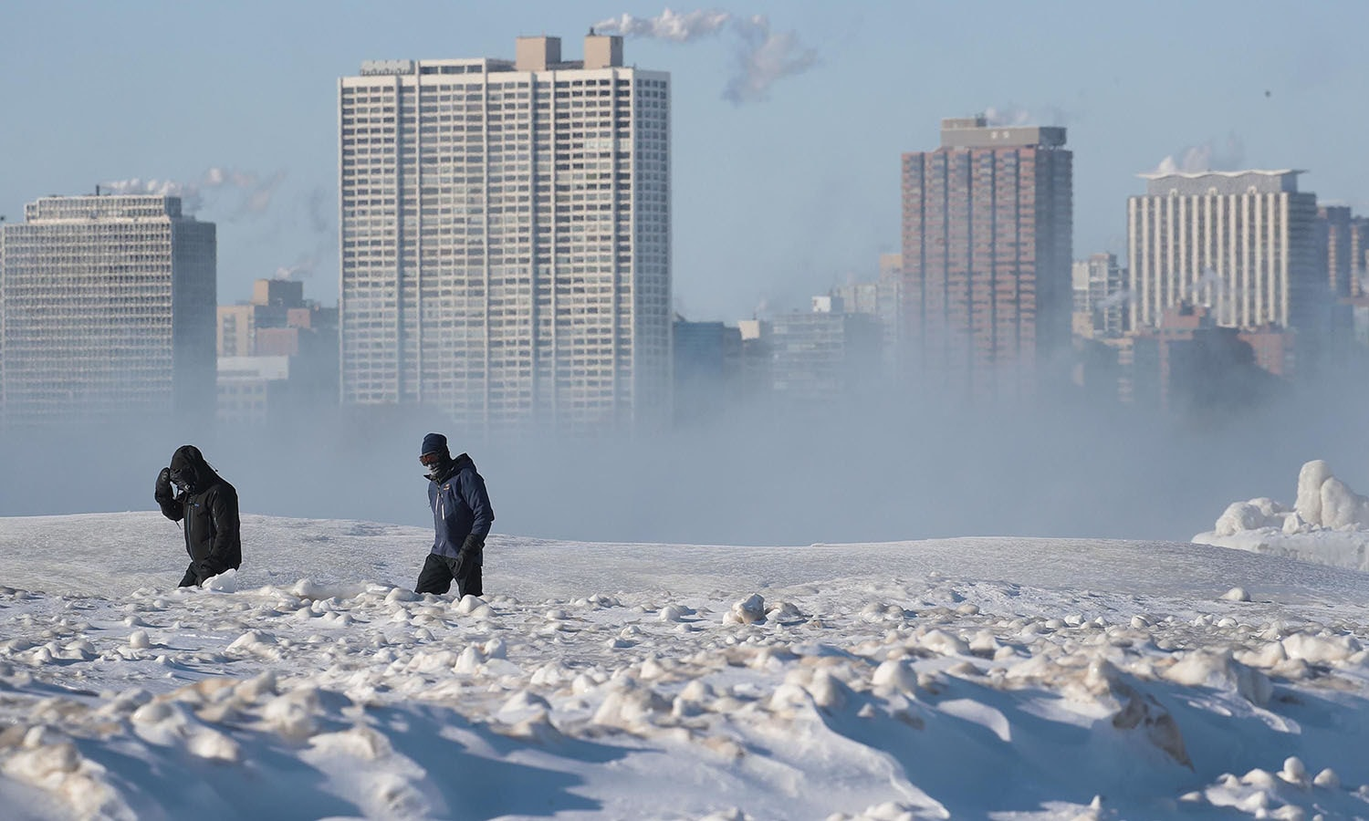 People walk along North Avenue Beach despite a temperature around -20 degrees. — AFP