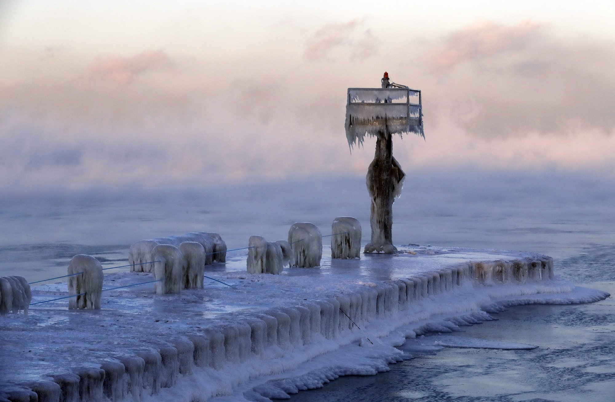 A harbor light is covered by snow and ice on the Lake Michigan at 39th Street Harbor. — AP