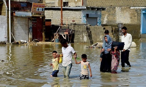 A family makes their way on a flooded street after heavy rain in Karachi in 2017. ─ AFP/File